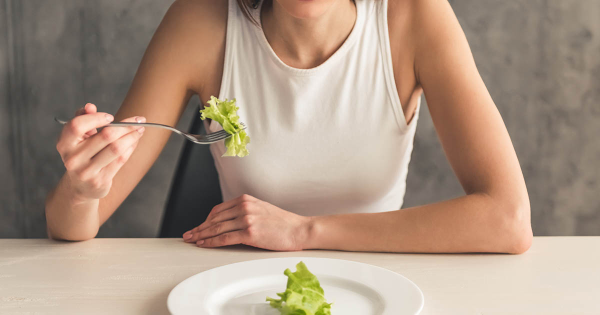 Woman sitting at a table with lettuce on her fork