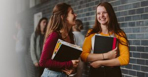 Two teenage girls in hallway at school holding textbooks