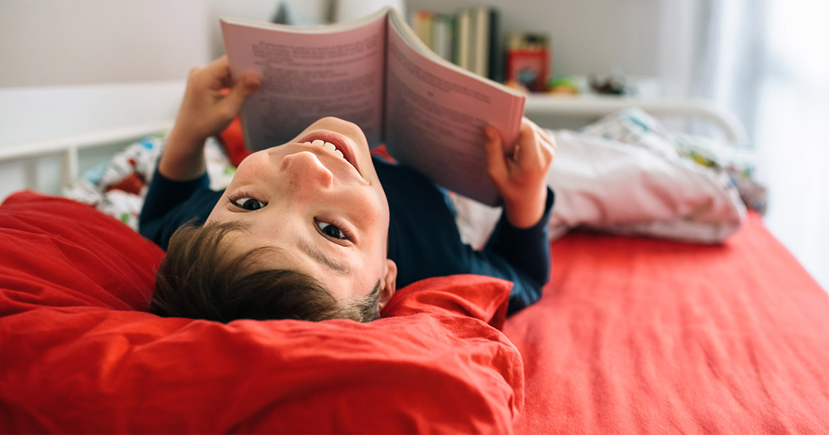 Small boy lying on back on bed, with book open