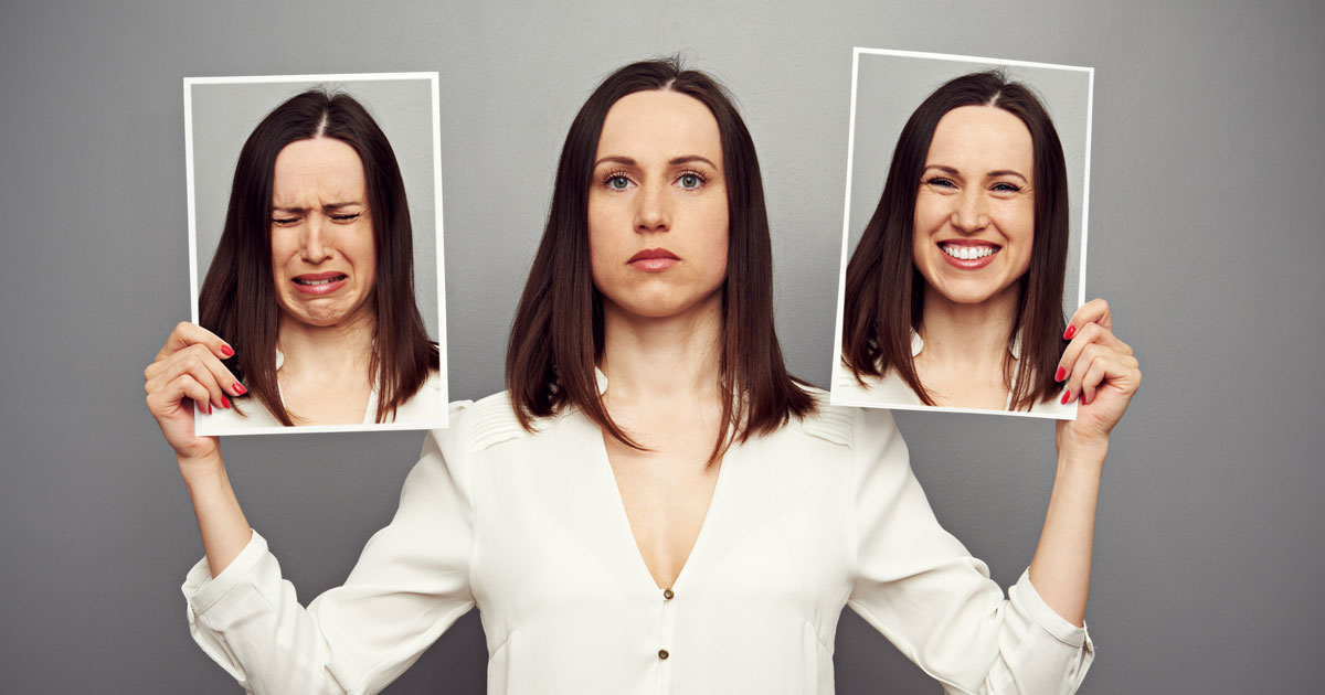 Woman holding two pictures of herself: one where she is crying and the other smiling