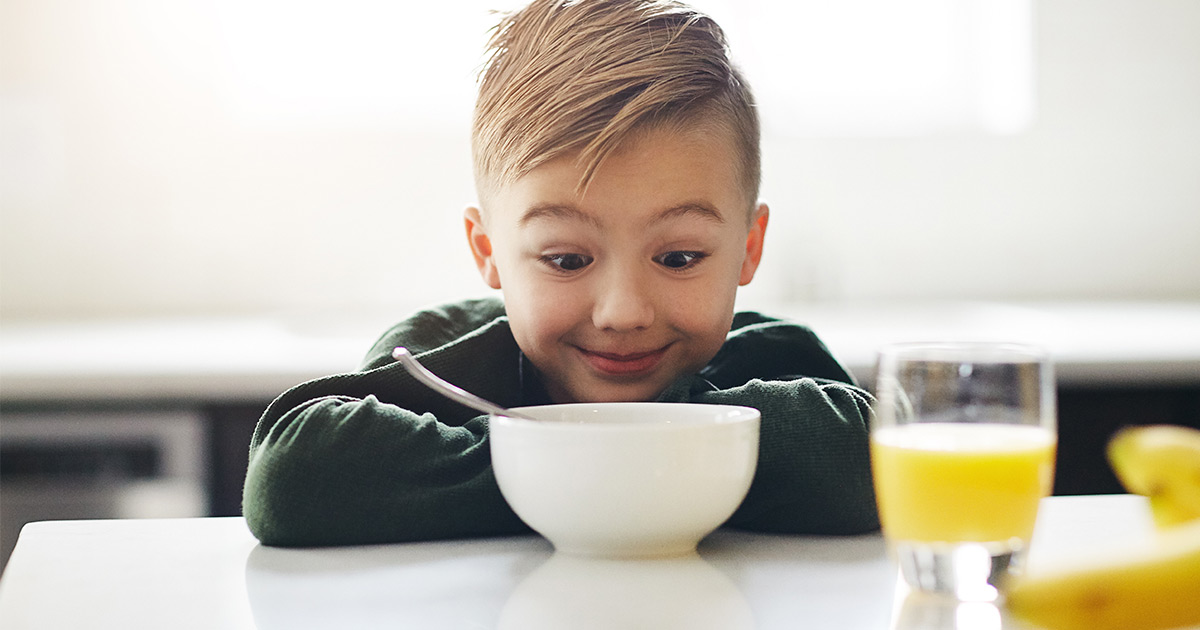 Small boy looking excitedly into his cereal bowl with glass of orange juice beside him