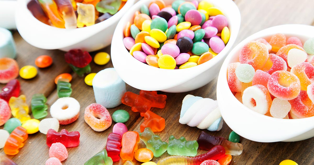Assorted candy in three bowls and spread on table