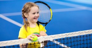 Small girl standing at net on a tennis court holding a racket and smiling