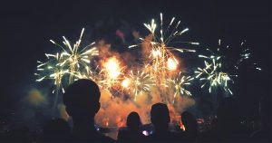 Firework display in sky with silhouetted people in foreground