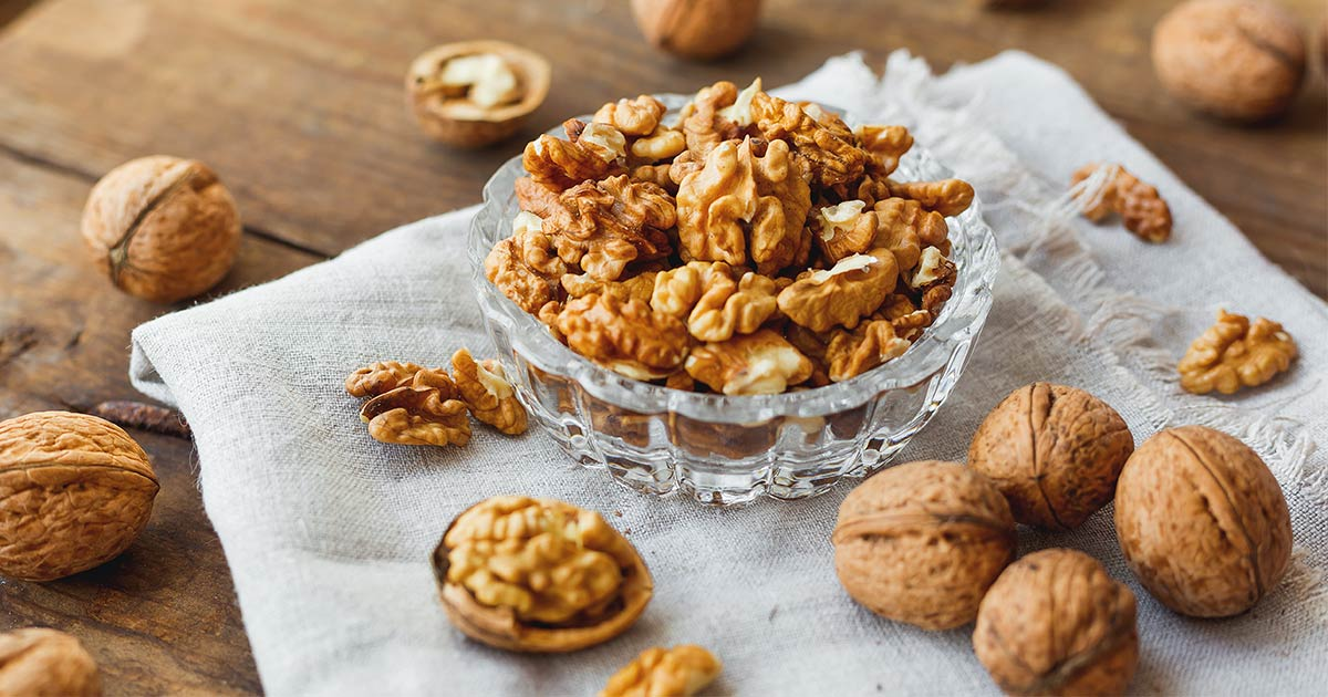Bowl of shelled walnuts with whole walnuts surrounding