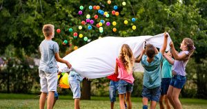 Kids holding bed sheet, throwing balls into air