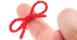 Red yarn tied around finger