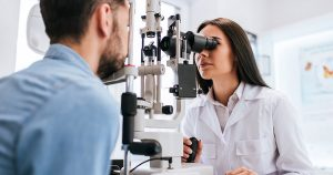 Eye doctor looking at man's eyes