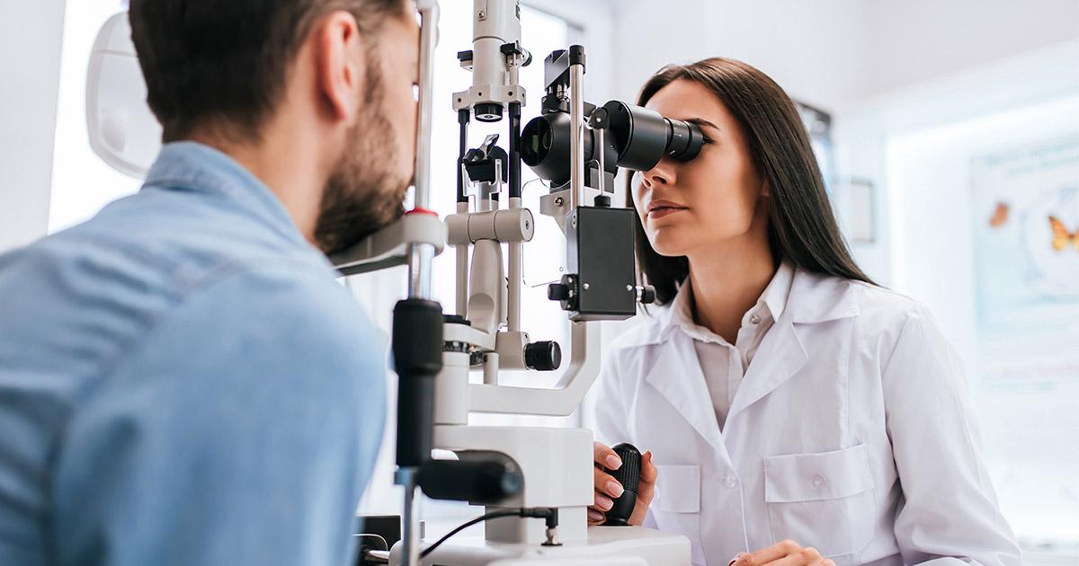 Eye doctor looking at man's eyes