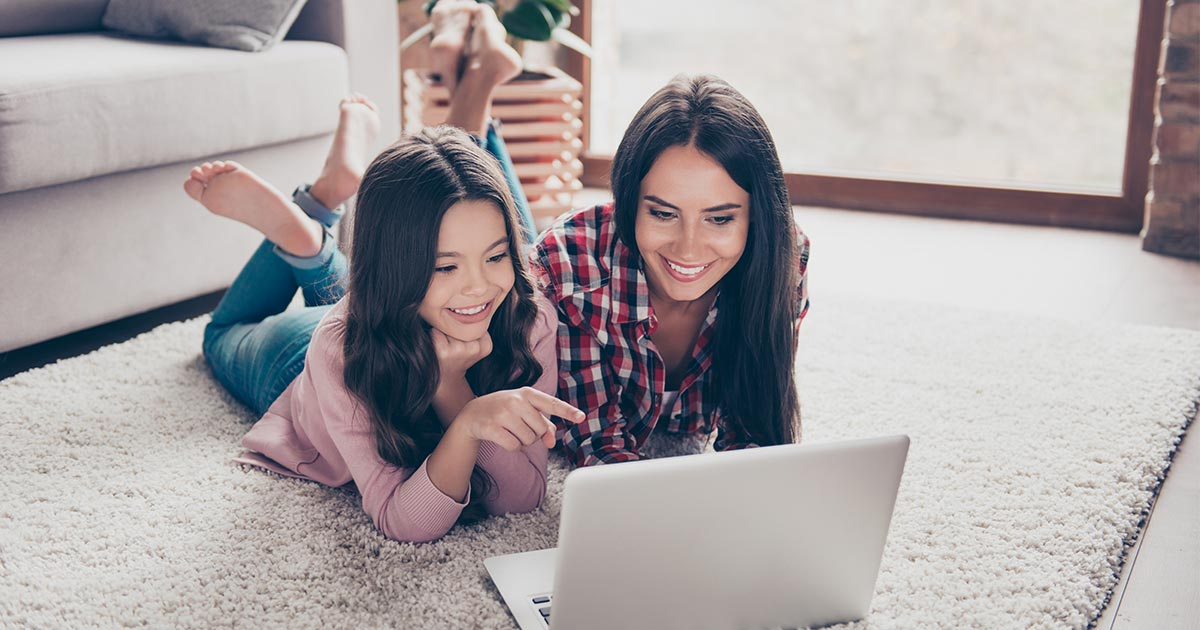 Mother and daughter lying on stomachs on floor looking at laptop screen