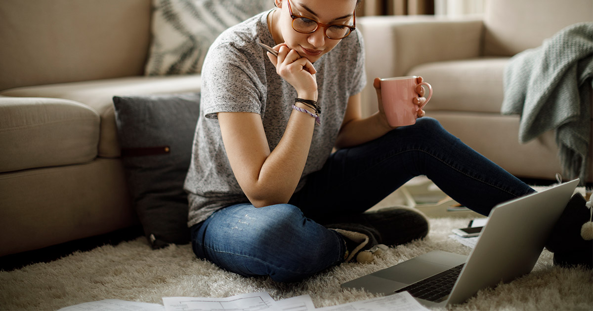 Woman sitting on floor with mug in hand, laptop open, and study notes on ground