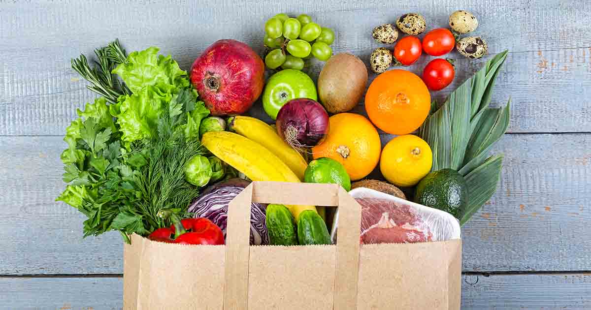 Fruits and vegetables spilling out of paper shopping bag