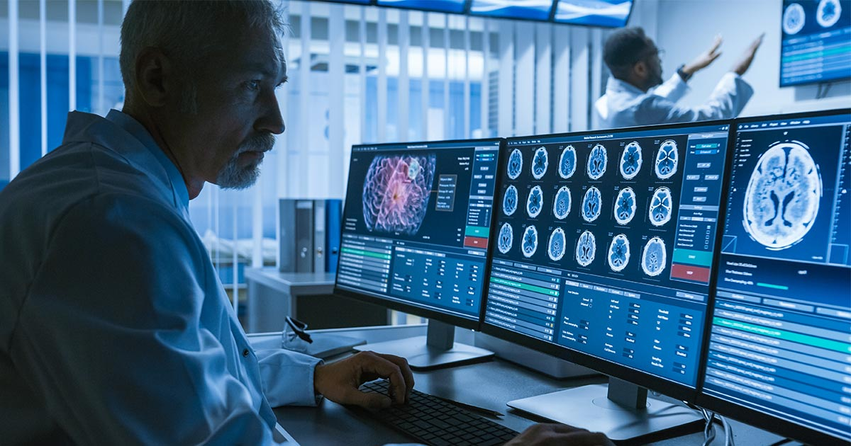 Doctor looking at various brain scans on three monitors