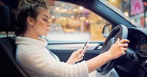 Woman looking at her cell phone while driving