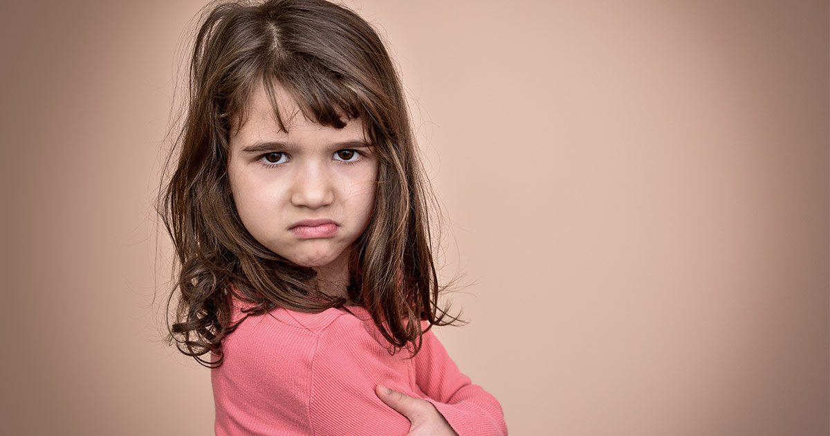 Little girl frowning and crossing arms