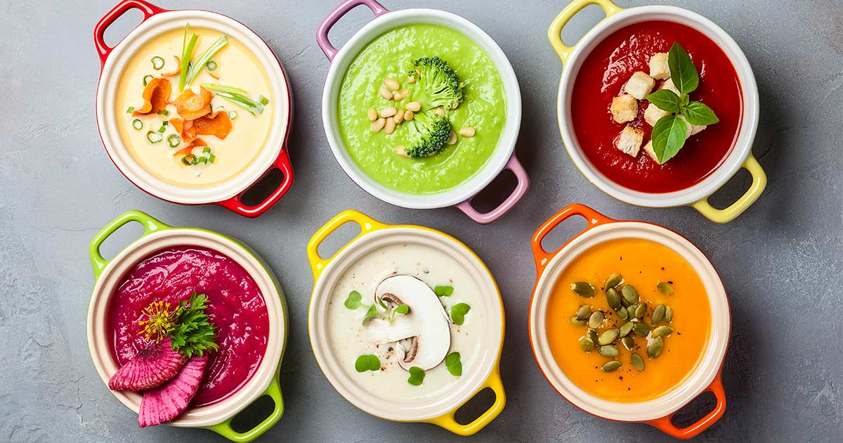 Six bowls of different colored soup