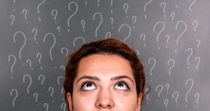 Woman looking upward with question marks drawn behind her