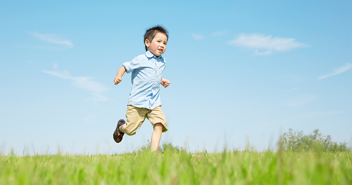 Boy running through a field