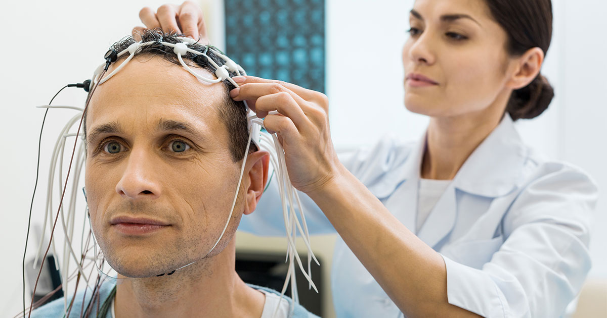 Man having electrodes attached to scalp by female doctor