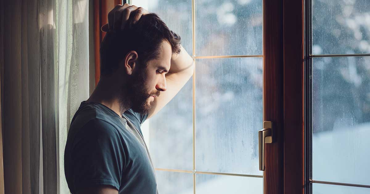 Man with hand on back of head, staring out window