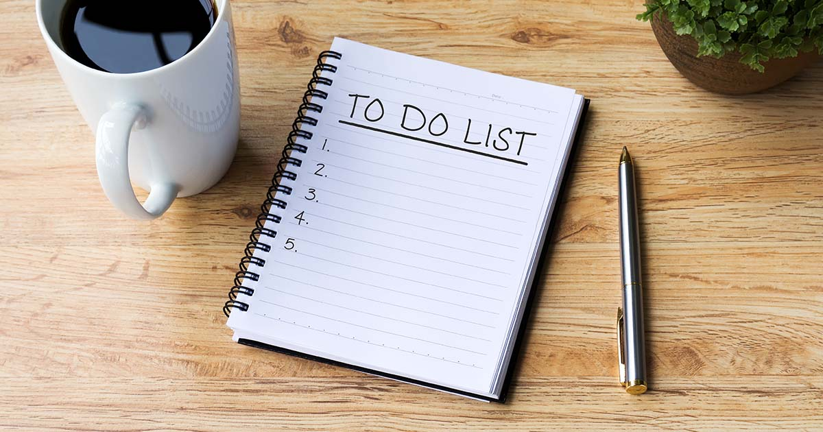 "Notebook with ""to do list"" written at top of page with pen to the right and mug to the left"