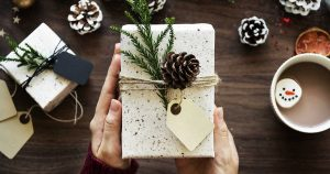 Wrapped gift with greenery and pinecone on top