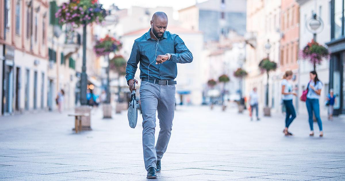 Man walking on sidewalk looking at watch