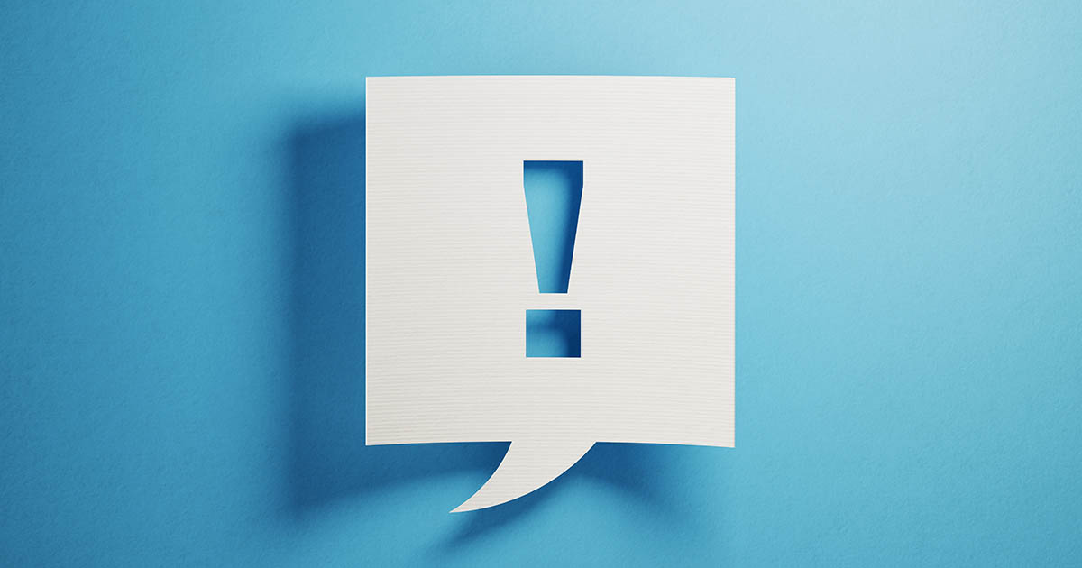 A cut-out exclamation point in a speech bubble.