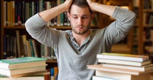 Man sitting at a desk with stacks of books looking stressed