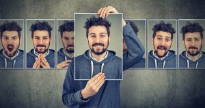 Man holding up different pictures of his face expressing different emotions