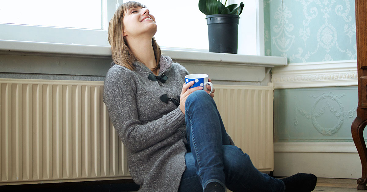 Woman sitting on ground with mug in hand, head leaned back, eyes closed, smiling.