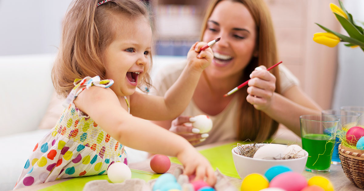 Mother and daughter painting eggs together