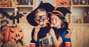Two kids wearing Halloween costumes and eating suckers