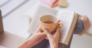 Woman holding coffee mug in front of an open book