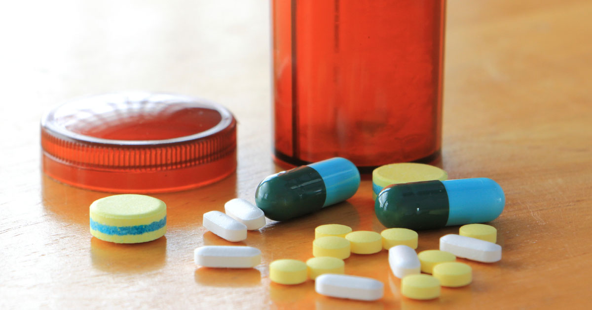 Pills in front of a bottle with lid off