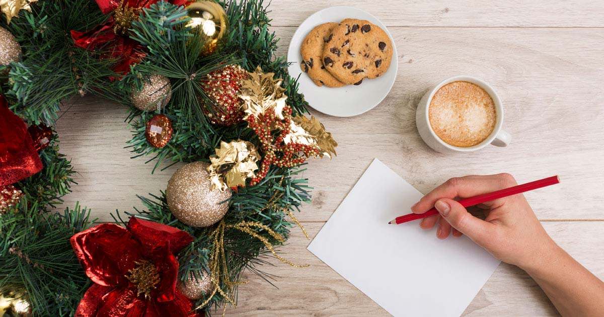 Christmas wreath, plate with cookie on it, latte, and person writing a list