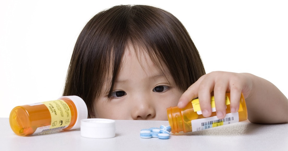 Little girl pouring pills out of a bottle