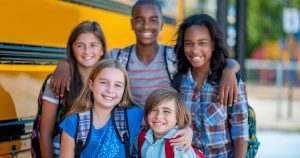 Kids with arms around each other in front of a school bus