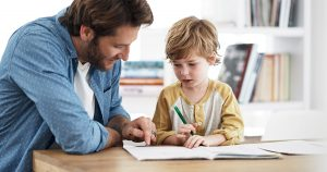 A Man helps his son with homework