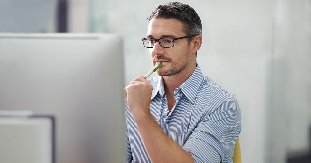 Man holding pen to lips and staring at computer monitor