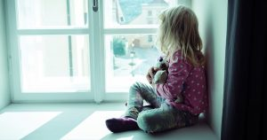 Little girl holding stuffed animal looking out window