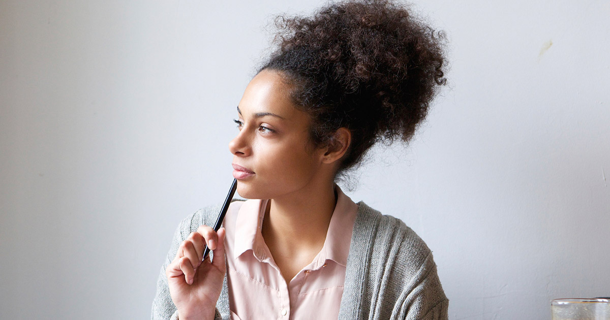 Woman staring into space thoughtfully, with tip of pen held to her bottom lip