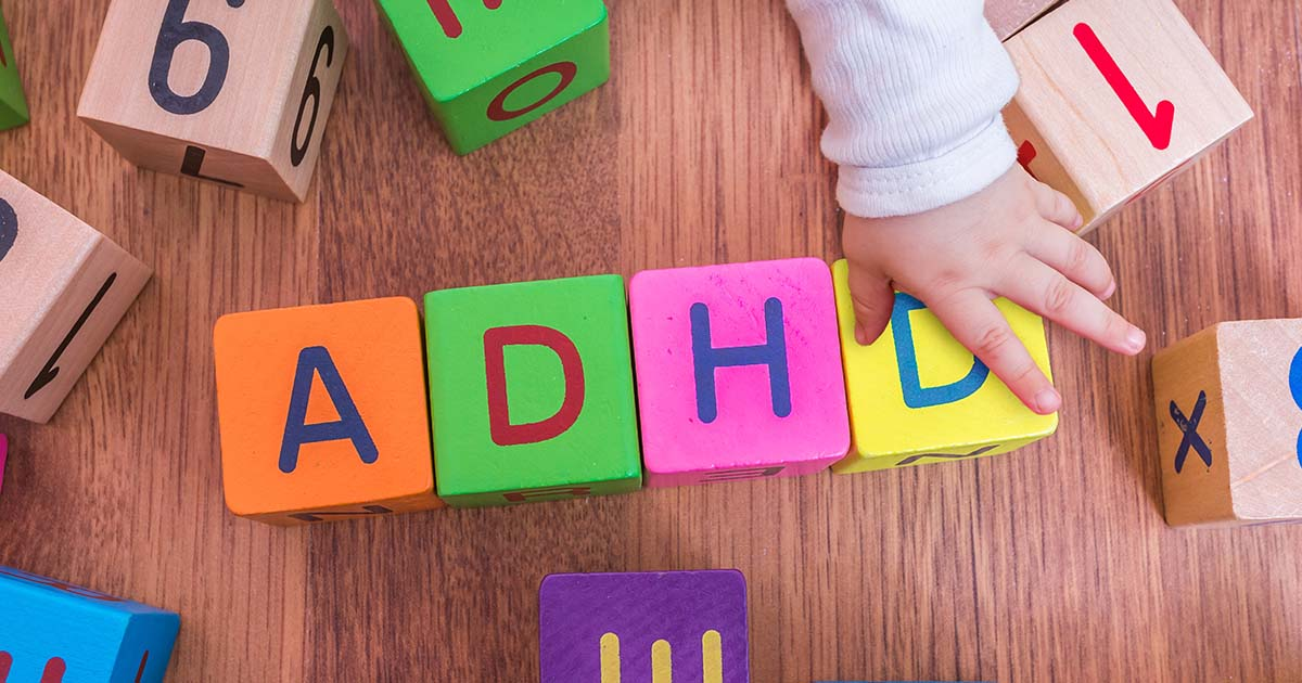 "Baby is playing with cubes with letters. The cubes together say ""ADHD"""