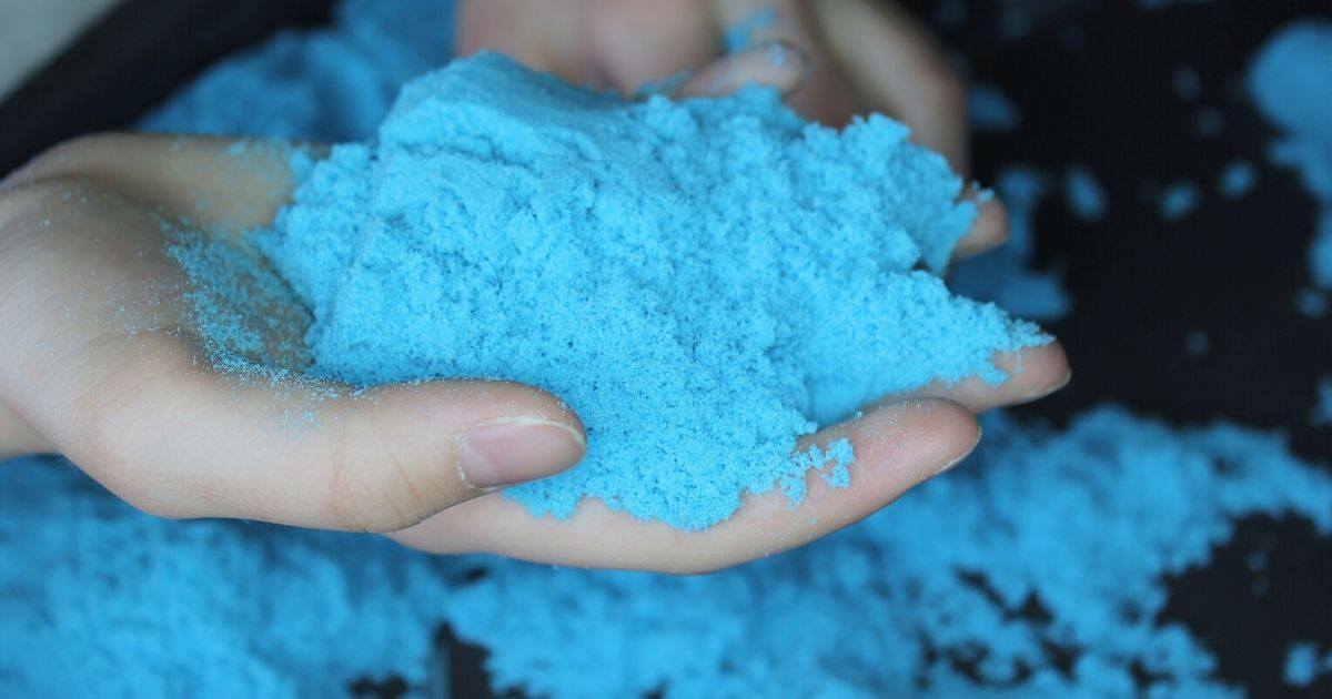 a boy holding blue kinetic sand, an example of toys for kids with ADHD