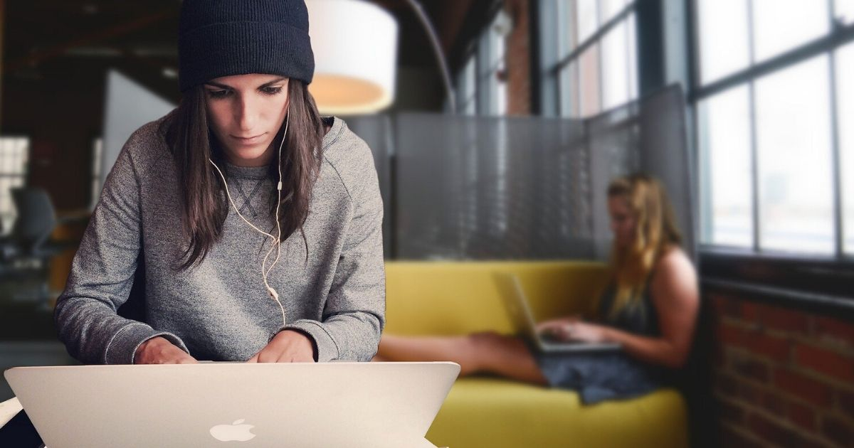 a female teenager studying on her laptop