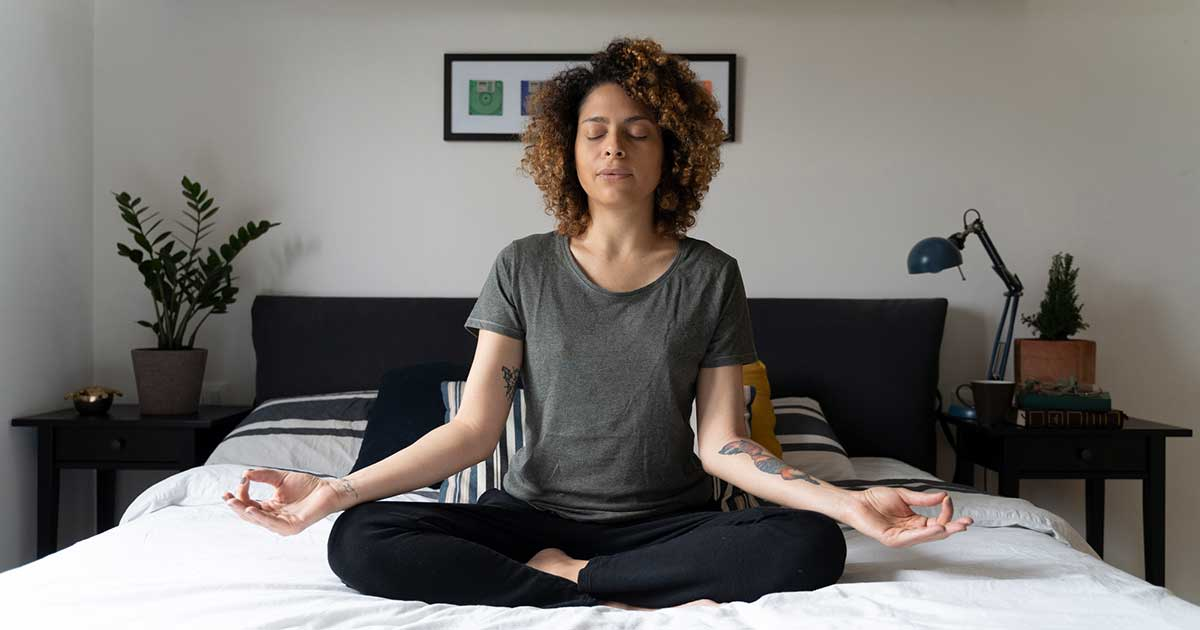 a woman practicing meditation on her bed