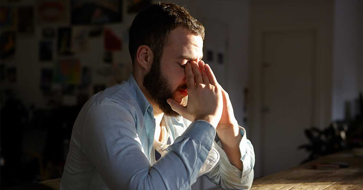 a man sitting anxiously at a table