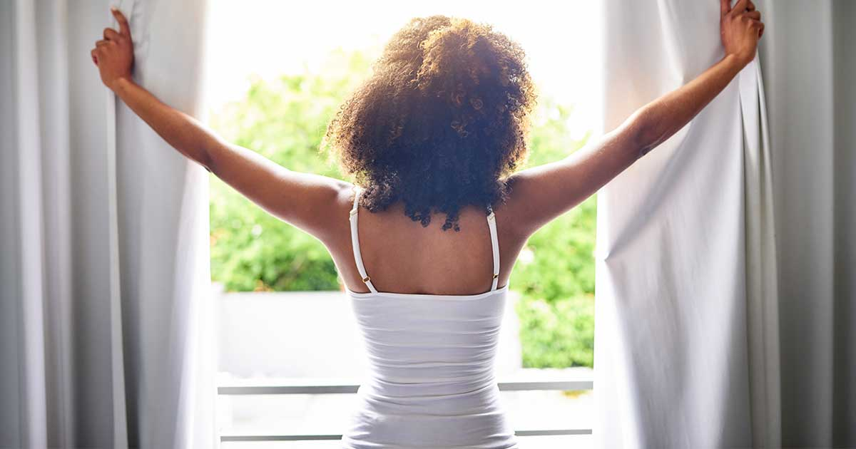 a woman opening her curtains in the morning