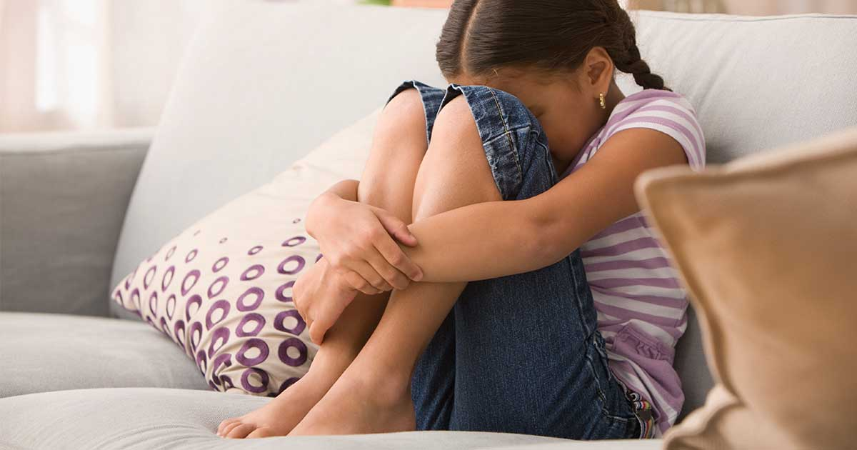 a young girl sitting with her head in her hands, overwhelmed by sensory overload